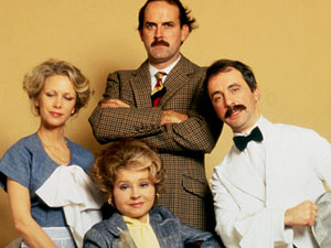 John Cleese a sBasil Fawlty with the cast of British sitcom Fawlty Towers