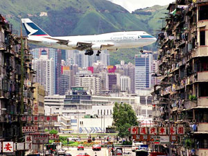 Cathay B747 roars over buildings landing at Kai Tak Airport, Hong Kong's old gateway