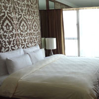 Cosmopolitan's Grand Deluxe room in gold with a harbour view