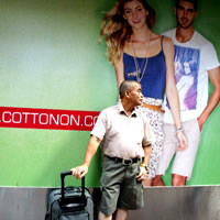 Man stands in front of Cotton On poster in Central, HK